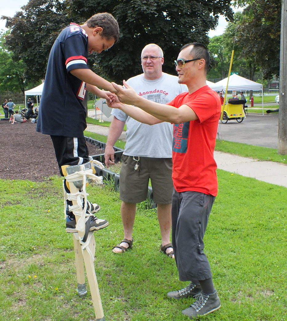 Masa teaches Cody how to stilt while his dad looks on at the Arts on Chicago Celebration.
