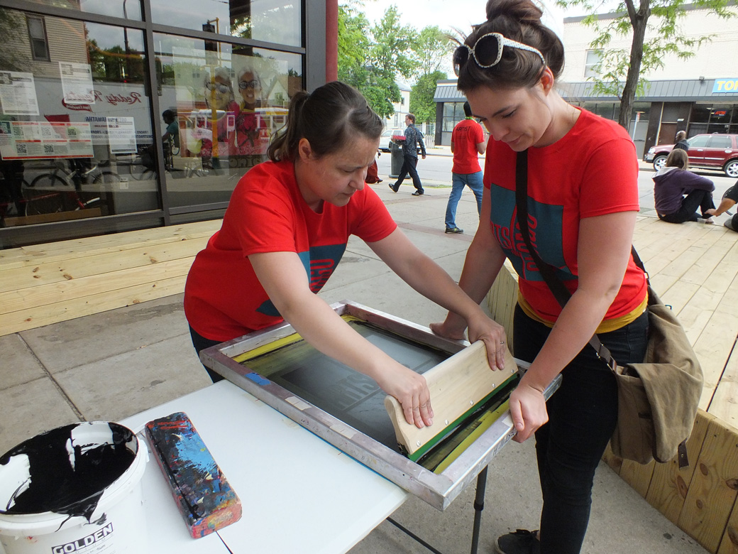 Natasha pulls a screen print at the June 8th Arts on Chicago celebration.