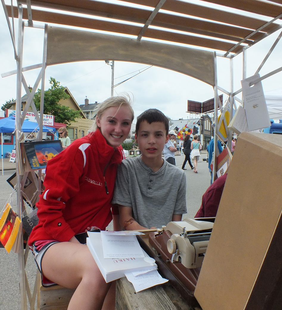 Anne and Thomas write a poem on the Poetry Mobile at the 38th and and Chicago Business Association festival.