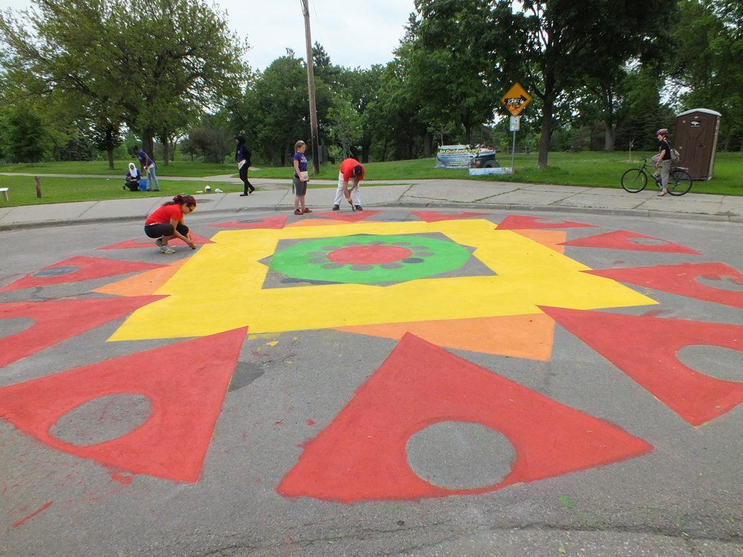Putting the finishing touches on the painted pavement on 10th Ave. and 34th Street.