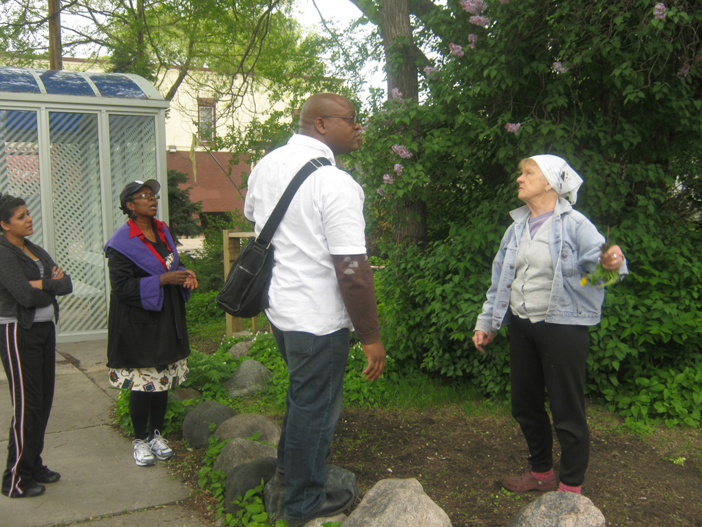 Christopher Deanes, Sabreen Hasan, and Rakhi Bisen on site with property owner Florence Hill (3201 Chicago ) where the unveiling of the new painting for the ArtStop Garden took place
