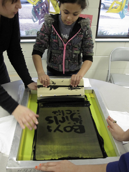 Natasha helps a kid at the Boys and Girls Club with screenprinting